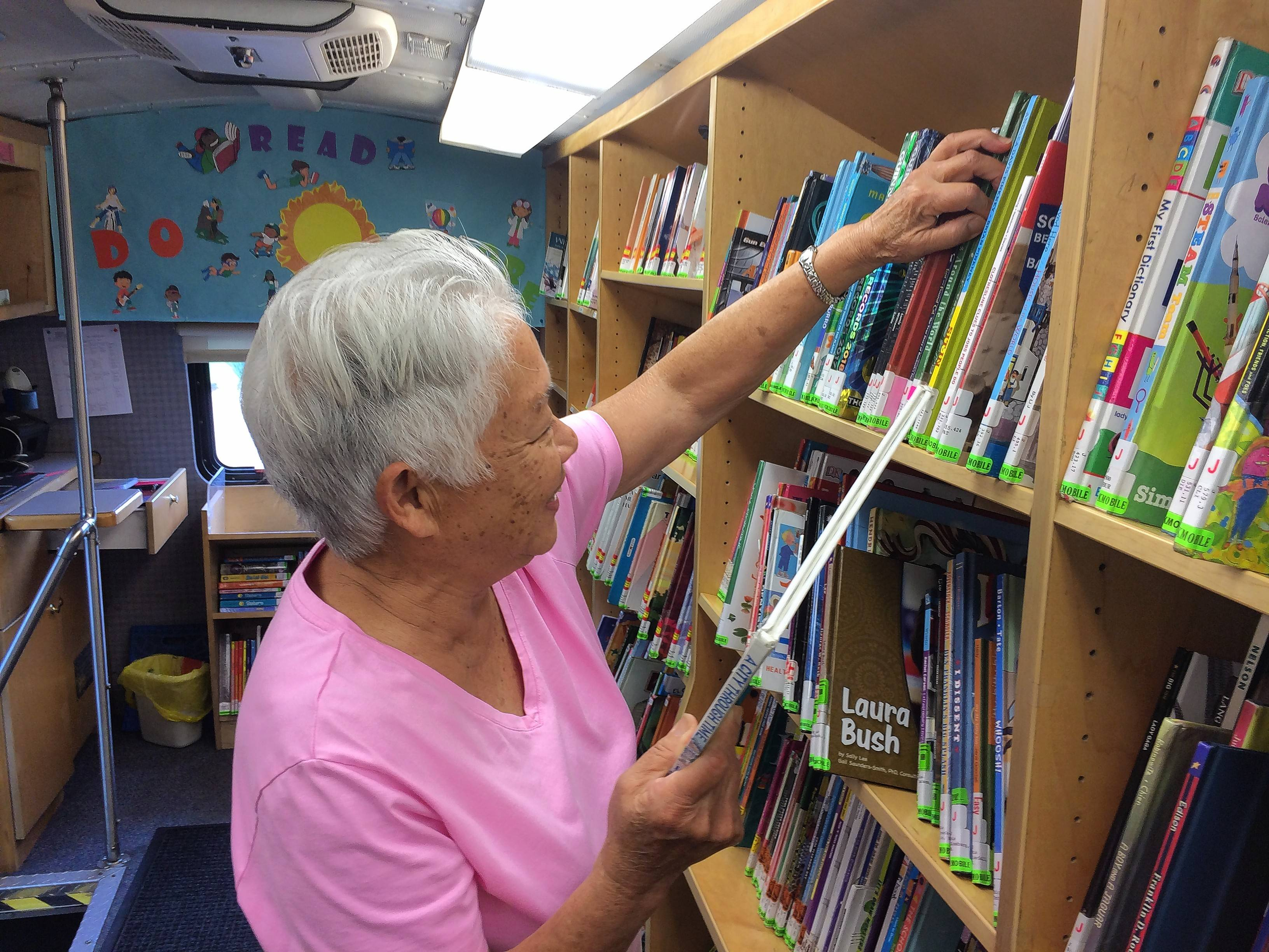 Driver Gail Tanimura shelves a book inside the Cook Memorial Public Library District's bookmobile.