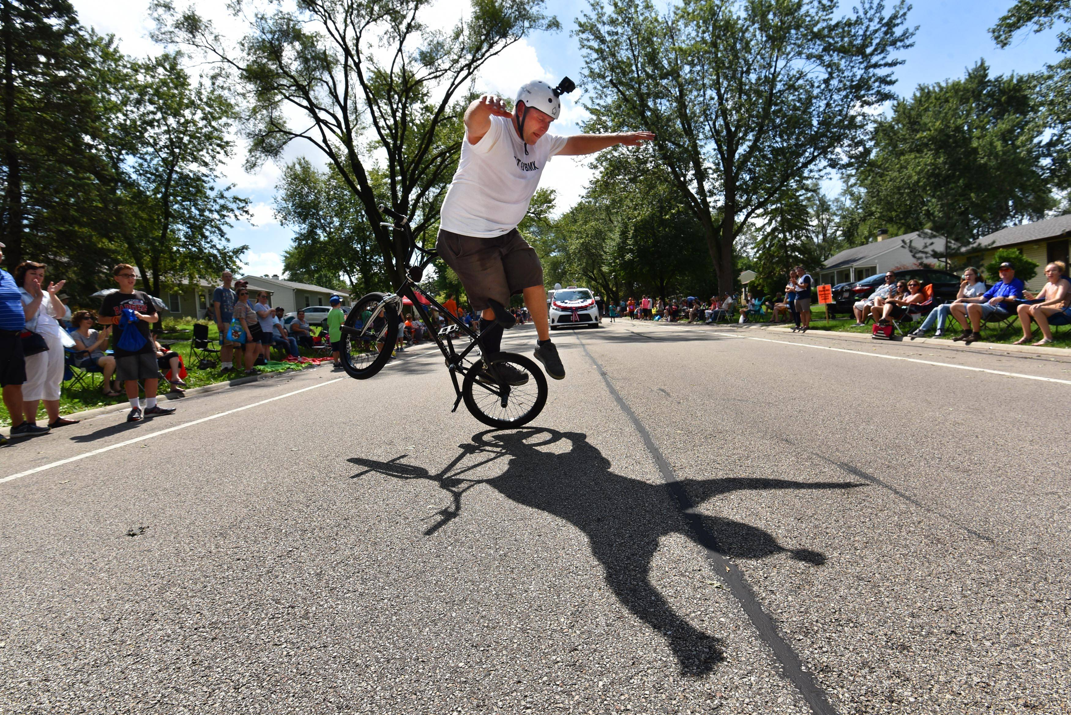 Todd Gully of Elk Grove Village performs on his bicycle in the middle of Raupp Boulevard at the Buffalo Grove Days parade Sunday morning. He rides with Flat 43 BMX in several parades annually.