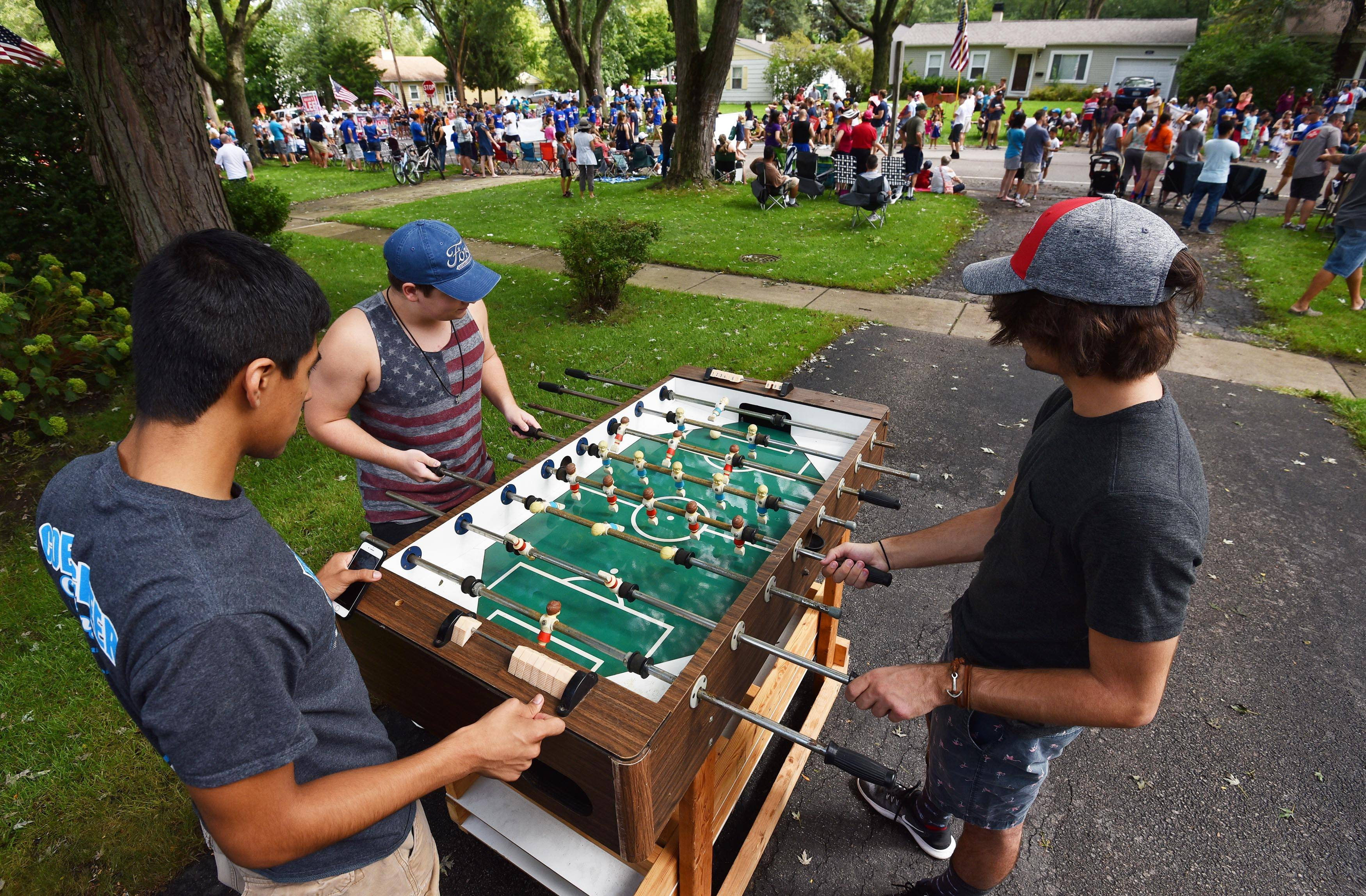 Erik Delgado, left, Connor Kotzenberg, middle, and Jared Cihler, right, play foosball in Kotzenberg's driveway Sunday morning as the Buffalo Grove Days parade ambles past along Raupp Boulevard.