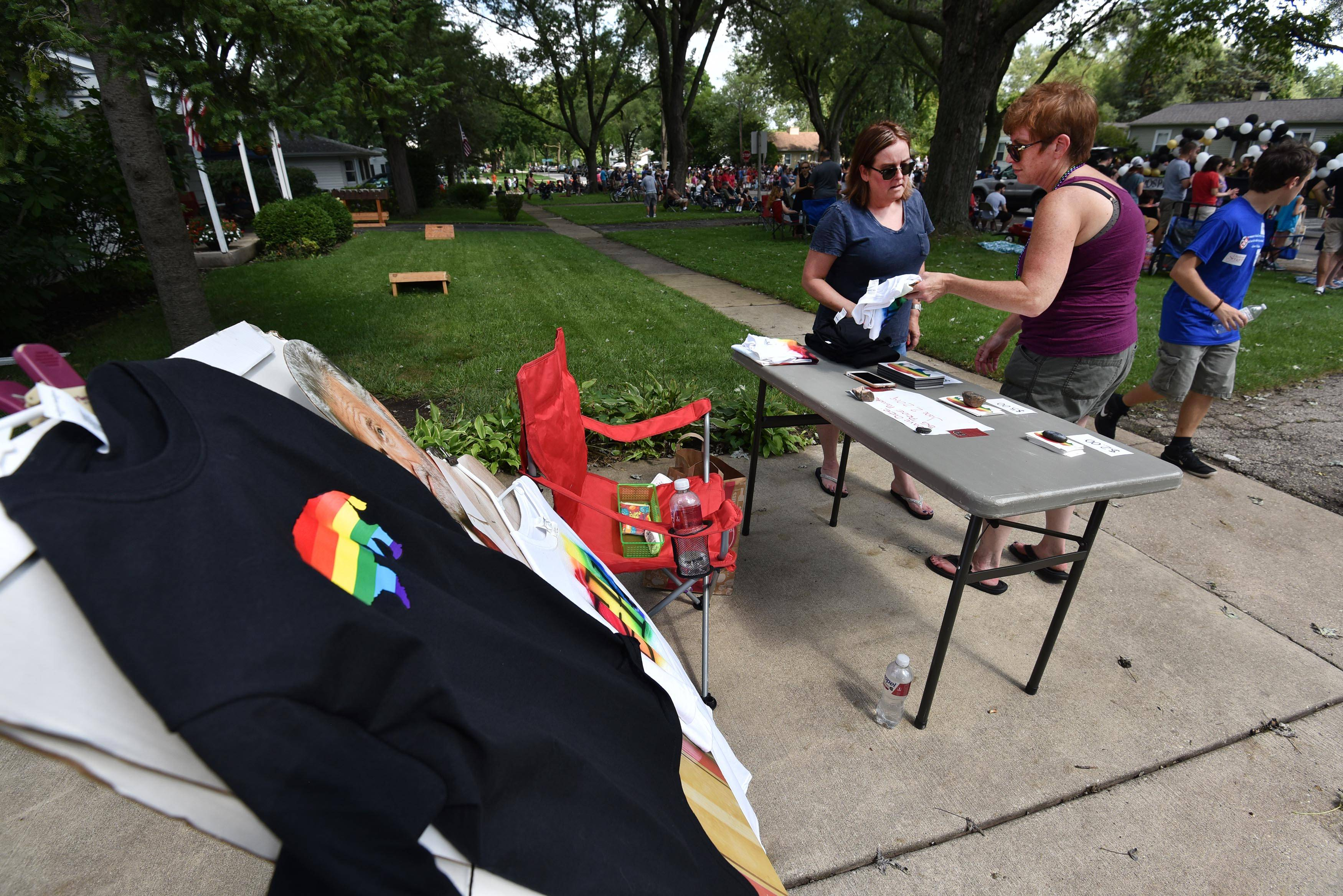 Lori Gayhart, right, shows a neighbor T-shirts for sale that promote the inaugural BG Pride parade, which is scheduled for next year. She and her daughter Grace, 17, were selling several items Sunday to help fund the pride parade effort at the Buffalo Grove Days parade.