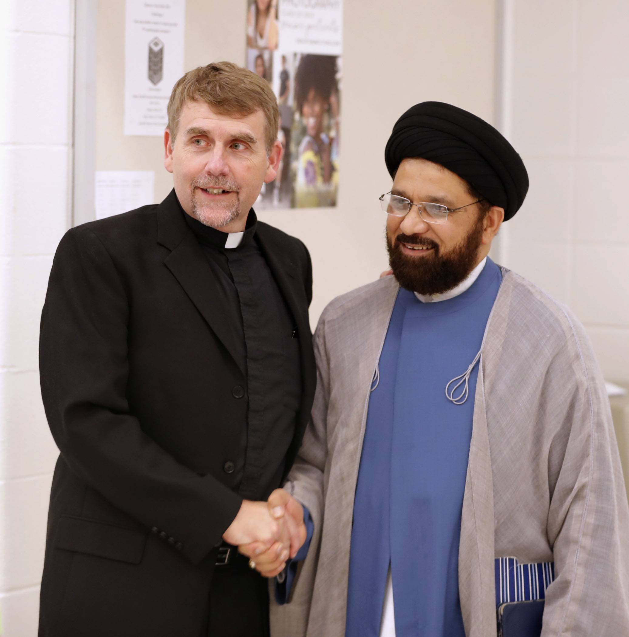 The Rev. Corey Brost, left, of St. Viator High School and Moulana Mehboob Mehdi of the Islamic Education Center in Glendale Heights meet during the Children of Abraham Coalition's seventh annual 9/11 interfaith Potluck For Peace Tuesday at St. Viator in Arlington Heights.