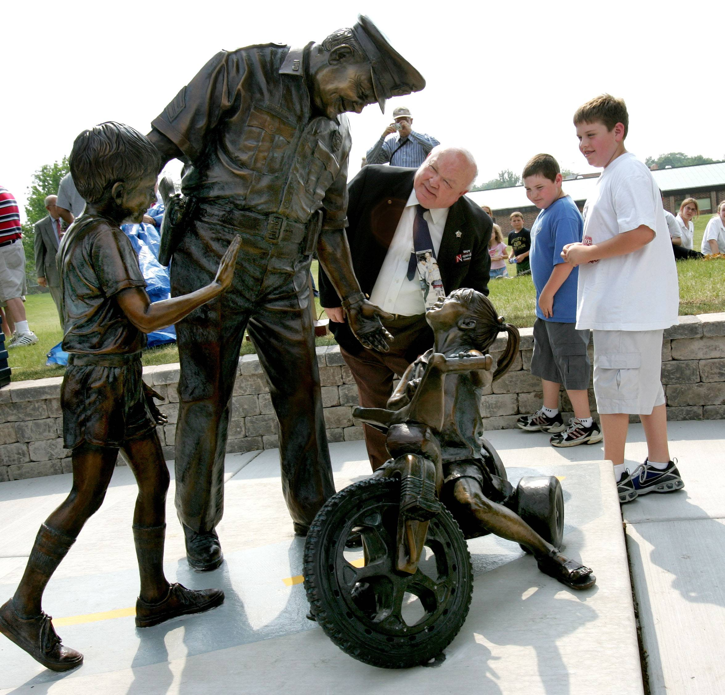 With his grandsons Zach and Nick, Pradel checks out his likeness during the unveiling of the Officer Friendly sculpture in front of Washington Junior High.