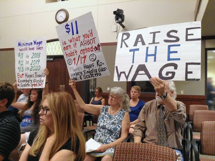 "Supporters of a higher minimum wage hold signs during an Arlington Heights village board meeting Tuesday to urge board members to ""opt in"" to Cook County's $11-an-hour rate."