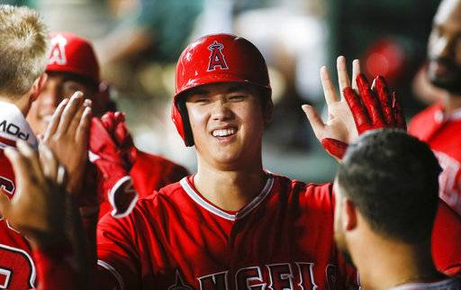 Los Angeles Angels' Shohei Ohtani smiles as he is greeted in the dugout by teammates after scoring on a single by Andrelton Simmons against the Texas Rangers during the seventh inning of a baseball game Wednesday, Sept. 5, 2018, in Arlington, Texas.