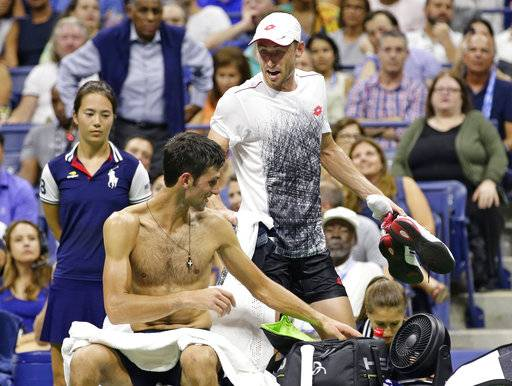 John Millman, top, of Australia, talks to Novak Djokovic, of Serbia, during the quarterfinals of the U.S. Open tennis tournament Wednesday, Sept. 5, 2018, in New York.