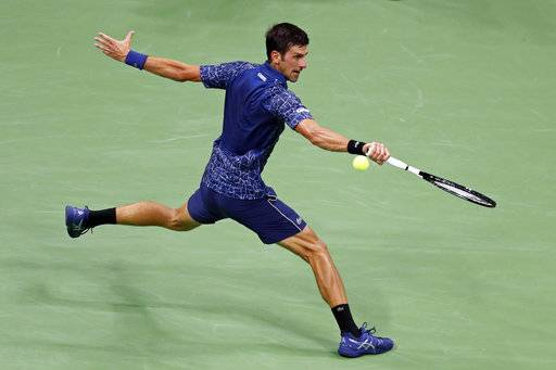 Novak Djokovic, of Serbia, reaches for a shot from John Millman, of Australia, during the quarterfinals of the U.S. Open tennis tournament Wednesday, Sept. 5, 2018, in New York.