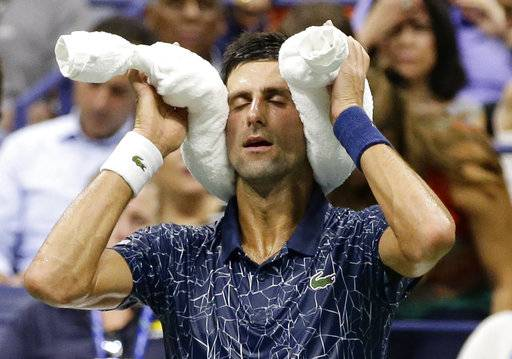 Novak Djokovic, of Serbia, sits during the changeover in a quarterfinal against John Millman, of Australia, of the U.S. Open tennis tournament Wednesday, Sept. 5, 2018, in New York.