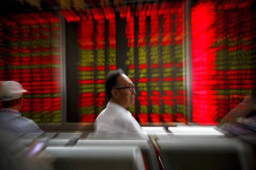 A man monitors stock prices with others at a brokerage house in Beijing, Thursday, Sept. 6, 2018. Asian markets are mixed on fears that the U.S. would soon impose tariffs on another $200 billion of Chinese goods, as public consultations draw to a close.