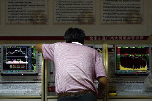 An investor checks stock prices at a brokerage house in Beijing, Thursday, Sept. 6, 2018. Asian markets are mixed on fears that the U.S. would soon impose tariffs on another $200 billion of Chinese goods, as public consultations draw to a close.
