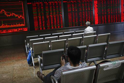 Investors monitor stock prices at a brokerage house in Beijing, Thursday, Sept. 6, 2018. Asian markets are mixed on fears that the U.S. would soon impose tariffs on another $200 billion of Chinese goods, as public consultations draw to a close.