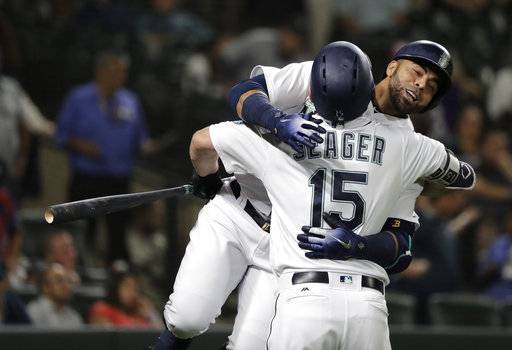 Seattle Mariners' Nelson Cruz, right, hugs Kyle Seager (15) after Cruz hit a solo home run during the fifth inning of a baseball game against the Baltimore Orioles, Wednesday, Sept. 5, 2018, in Seattle. The homer was back-to-back with one hit by Mariners' Denard Span.