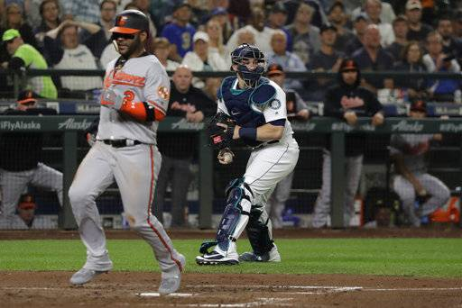 Baltimore Orioles' Jonathan Villar, left, scores on a fielding error by Seattle Mariners shortstop Jean Segura as catcher Mike Zunino, right, holds the ball during the fifth inning of a baseball game Wednesday, Sept. 5, 2018, in Seattle.