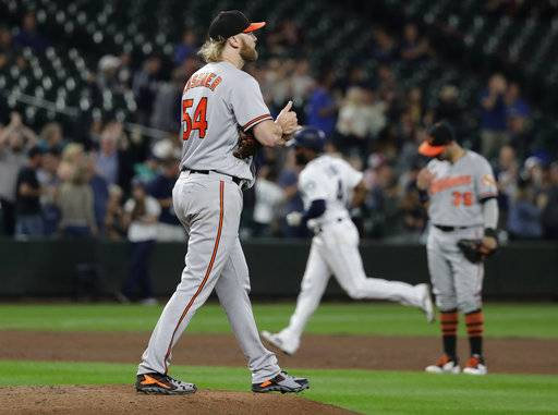 Baltimore Orioles starting pitcher Andrew Cashner, left, stands on the mound after he gave up a solo home run to Seattle Mariners' Denard Span, rounding the bases second from right, during the fifth inning of a baseball game Wednesday, Sept. 5, 2018, in Seattle. The homer was back-to-back with one hit by Mariners' Nelson Cruz.