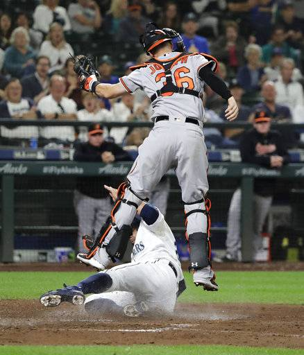 Seattle Mariners' Nelson Cruz is safe at home as he slides under Baltimore Orioles catcher Caleb Joseph to score on a single by Denard Span during the seventh inning of a baseball game Wednesday, Sept. 5, 2018, in Seattle.