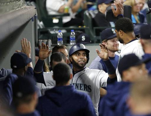 Seattle Mariners' Nelson Cruz smiles in the dugout after he scored on a single by Denard Span during the seventh inning of the team's baseball game against the Baltimore Orioles, Wednesday, Sept. 5, 2018, in Seattle.