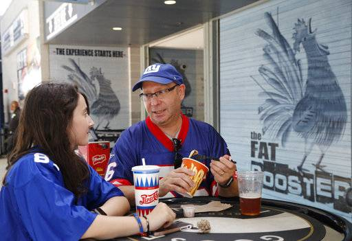 In a photo taken Thursday, Aug. 30, 2018, Todd Silva, right, and his daughter Audrey Silva eat fries at the Fat Rooster restaurant at MetLife Stadium prior to an NFL preseason football game between the New York Giants and the New England Patriots in East Rutherford, N.J. With the start of the NFL season, teams hit the field trying to show just how much they've improved. In the stands, the pressure is just as intense when it comes to feeding fans. Chefs spend weeks and months each offseason scheming up tasty new dishes to help lure people away from their couches and big-screen televisions into NFL stadiums and up to concession stands.