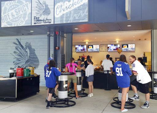 In a photo taken Thursday, Aug. 30, 2018, football fans enjoy a bite at the Fat Rooster restaurant at MetLife Stadium prior to an NFL preseason football game between the New York Giants and the New England Patriots in East Rutherford, N.J. With the start of the NFL season, teams hit the field trying to show just how much they've improved. In the stands, the pressure is just as intense when it comes to feeding fans. Chefs spend weeks and months each offseason scheming up tasty new dishes to help lure people away from their couches and big-screen televisions into NFL stadiums and up to concession stands.