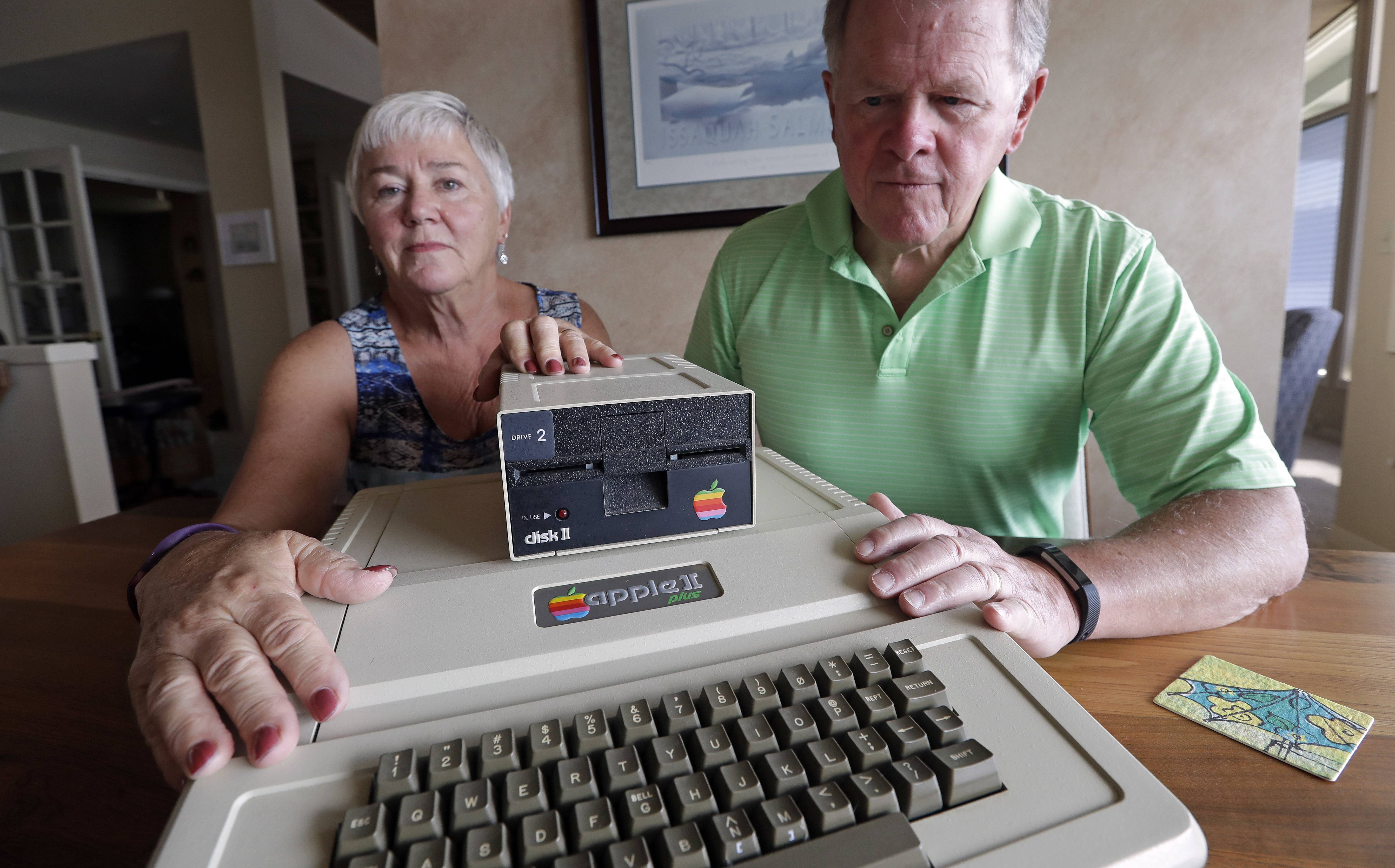 "Kathy and Steve Dennis display their 1980's-era Apple II+ computer bought for their then young sons in Bellevue, Wash. Three decades ago they never heard the phrase ""screen time,"" nor did they worry much about limiting the time the kids spent with technology, considering the computer an investment in their future. Things have changed with their grandkids and their phones."