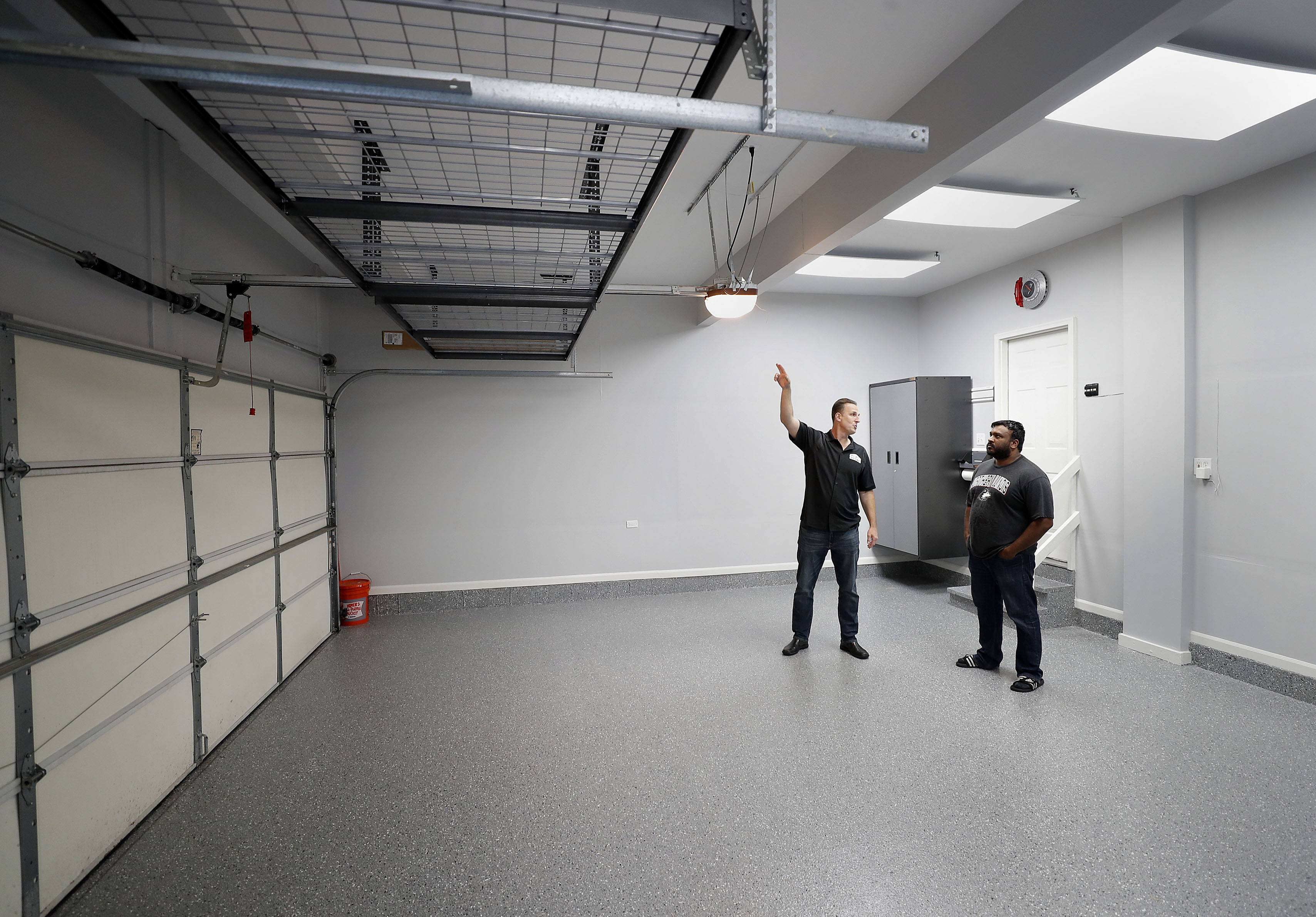 Mathew Joseph, right, of Vernon Hills and Garage Store owner Jim Melchert look at new overhead racks that were installed in Joseph's garage after he won a Garage Makeover contest.