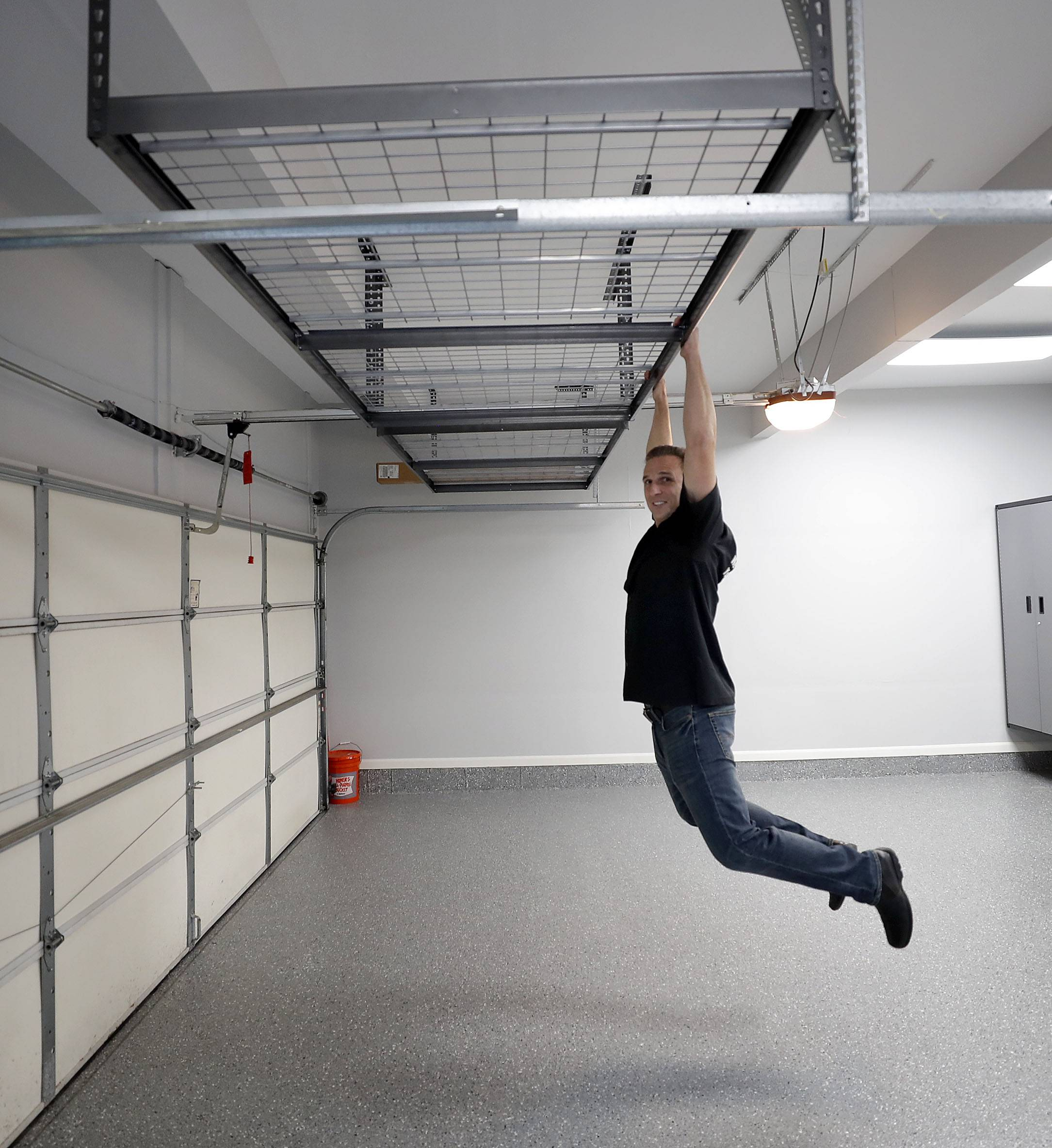 Garage Store owner Jim Melchert shows the strength of an overhead storage rack installed in Matt Joseph's garage in Vernon Hills.