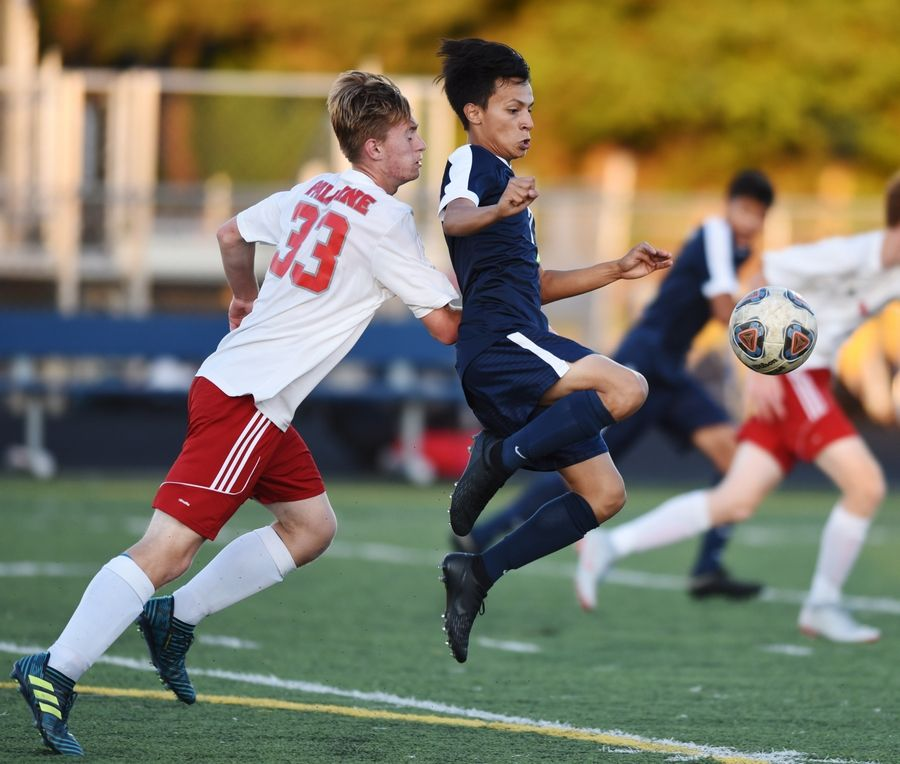 Conant's Mauricio Flores gets in front of Palatine's Brian Sobkowiak during Tuesday's soccer match in Hoffman Estates.