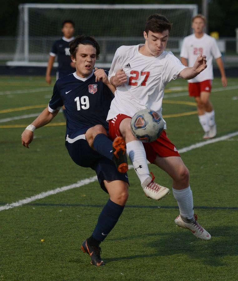 Conant's Joshua Kaye, left, and Palatine's Matt Geisel pursue the ball during Tuesday's soccer match in Hoffman Estates.