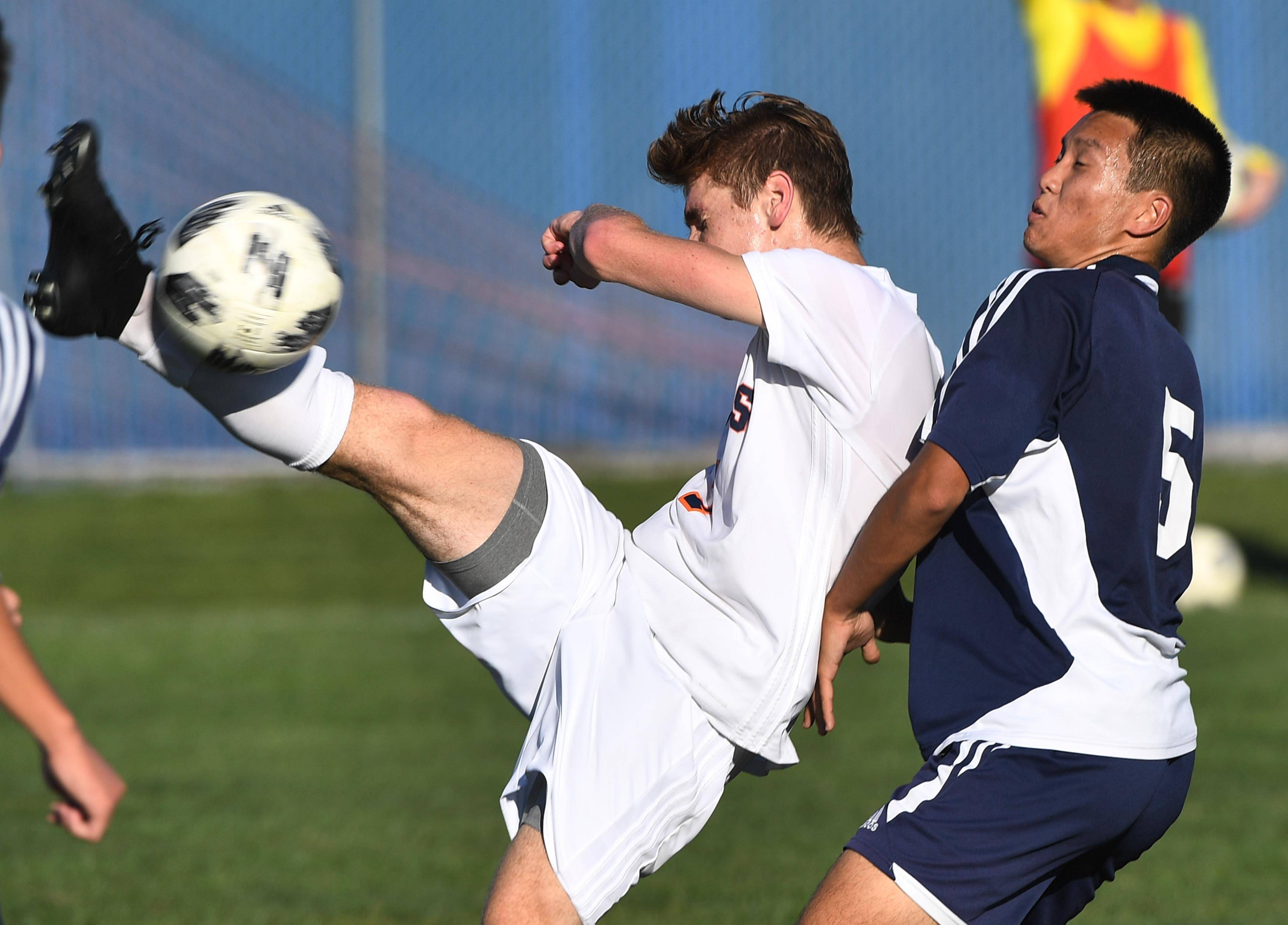 Naperville North's Patrick Koenig bicycle kicks the ball against Neuqua Valley's Kevin Wu in a boys soccer game Tuesday in Naperville.