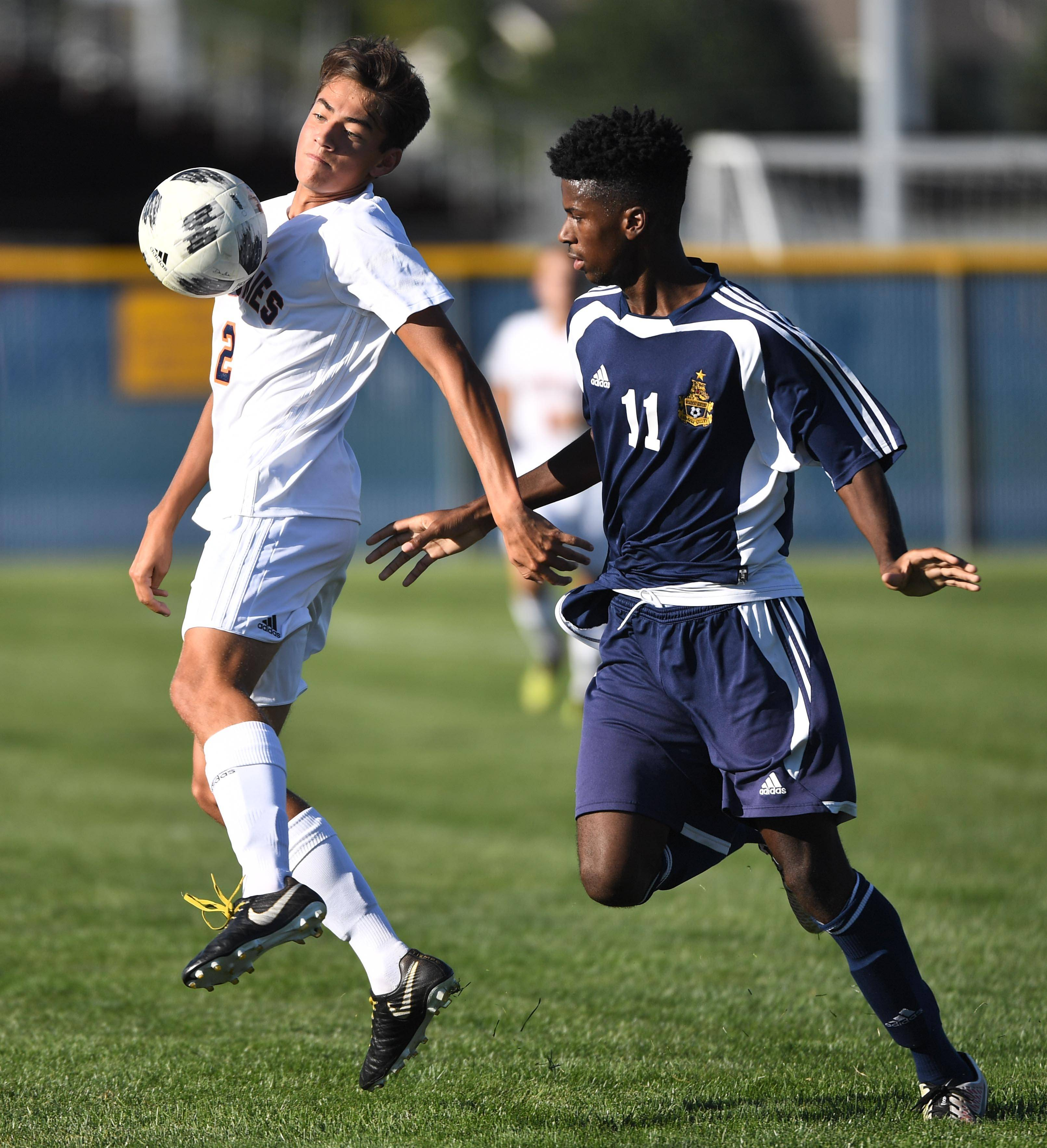 Naperville North's Jacob Vrankinin keeps the ball away from Neuqua Valley's Ben Head a boys soccer game Tuesday in Naperville.