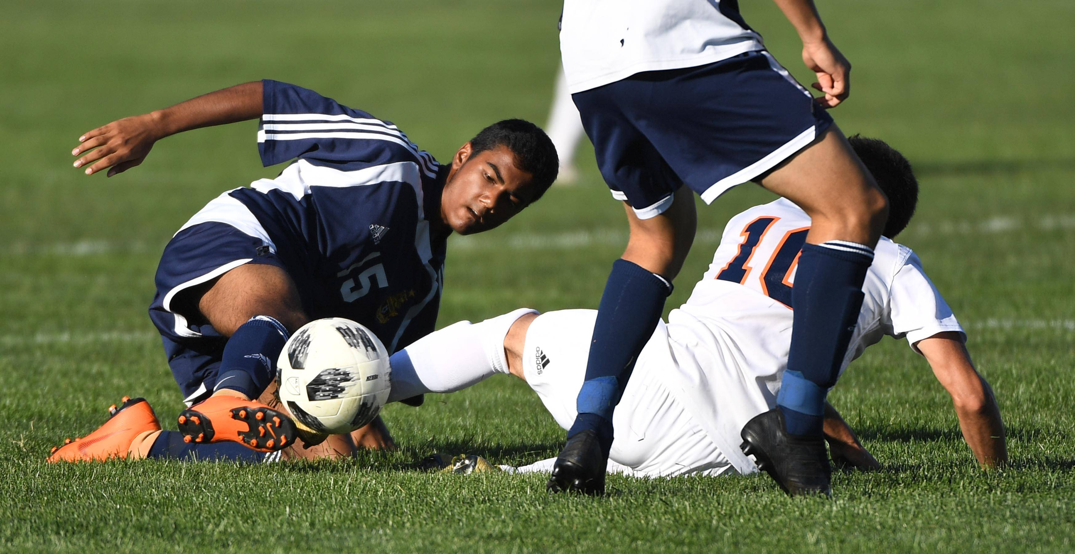 Neuqua Valley's Kevin Wu, left, and Naperville North's Ali Khorfan battle for the ball from the ground in a boys soccer game Tuesday in Naperville.