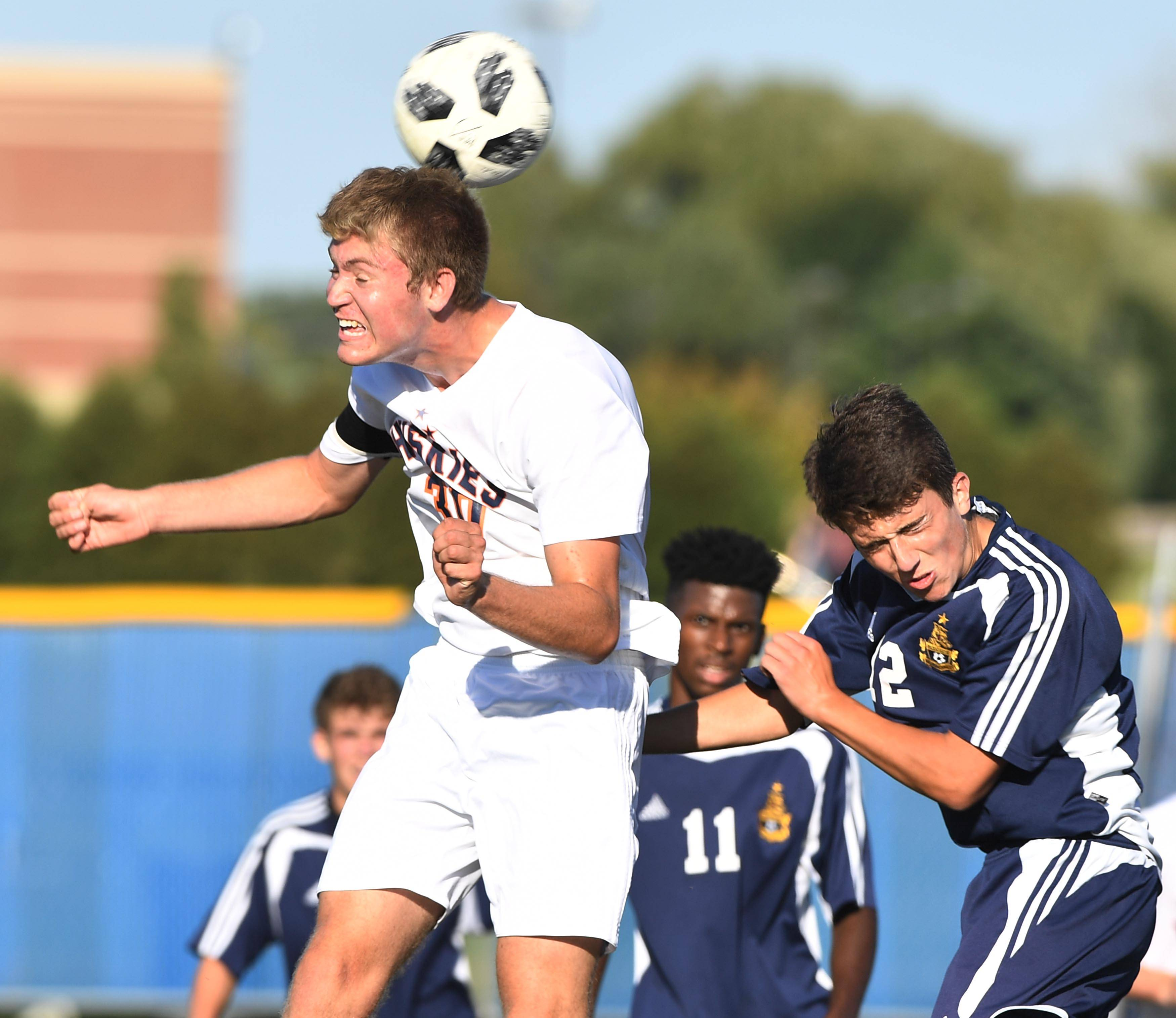 Naperville North's Colin Iverson heads the ball in front of Neuqua Valley's Mav Lehman in a boys soccer game Tuesday in Naperville.