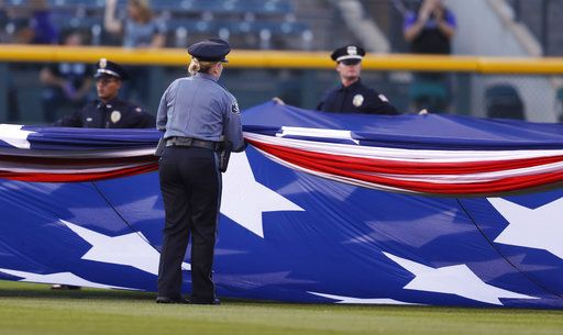 Police officers unfurl an American flag to mark the anniversary of the 9/11 terrorist attacks during a ceremony before a baseball game against the Arizona Diamondbacks, Tuesday, Sept. 11, 2018, in Denver.