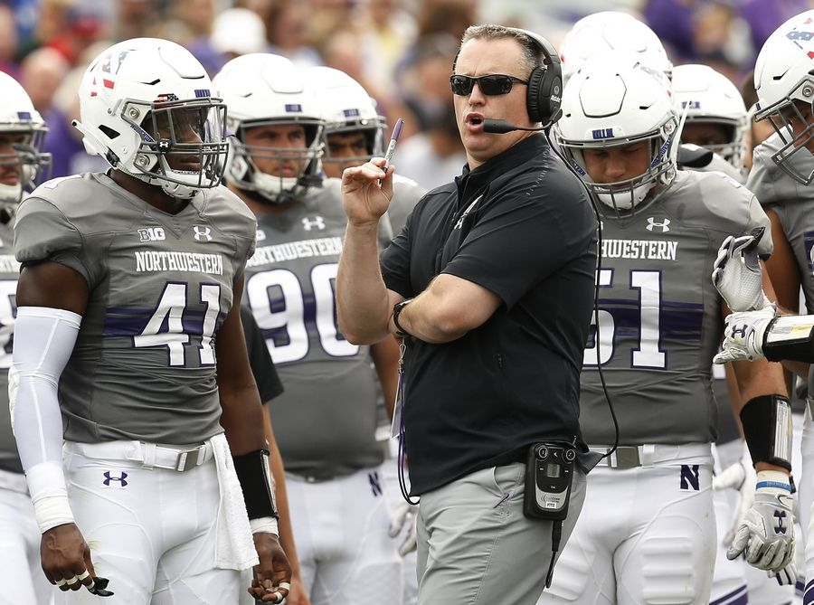 Northwestern coach Pat Fitzgerald, center, speaks with his team during a break in the play in an NCAA college football game against Duke Saturday, Sept. 8, 2018, in Evanston, Ill.