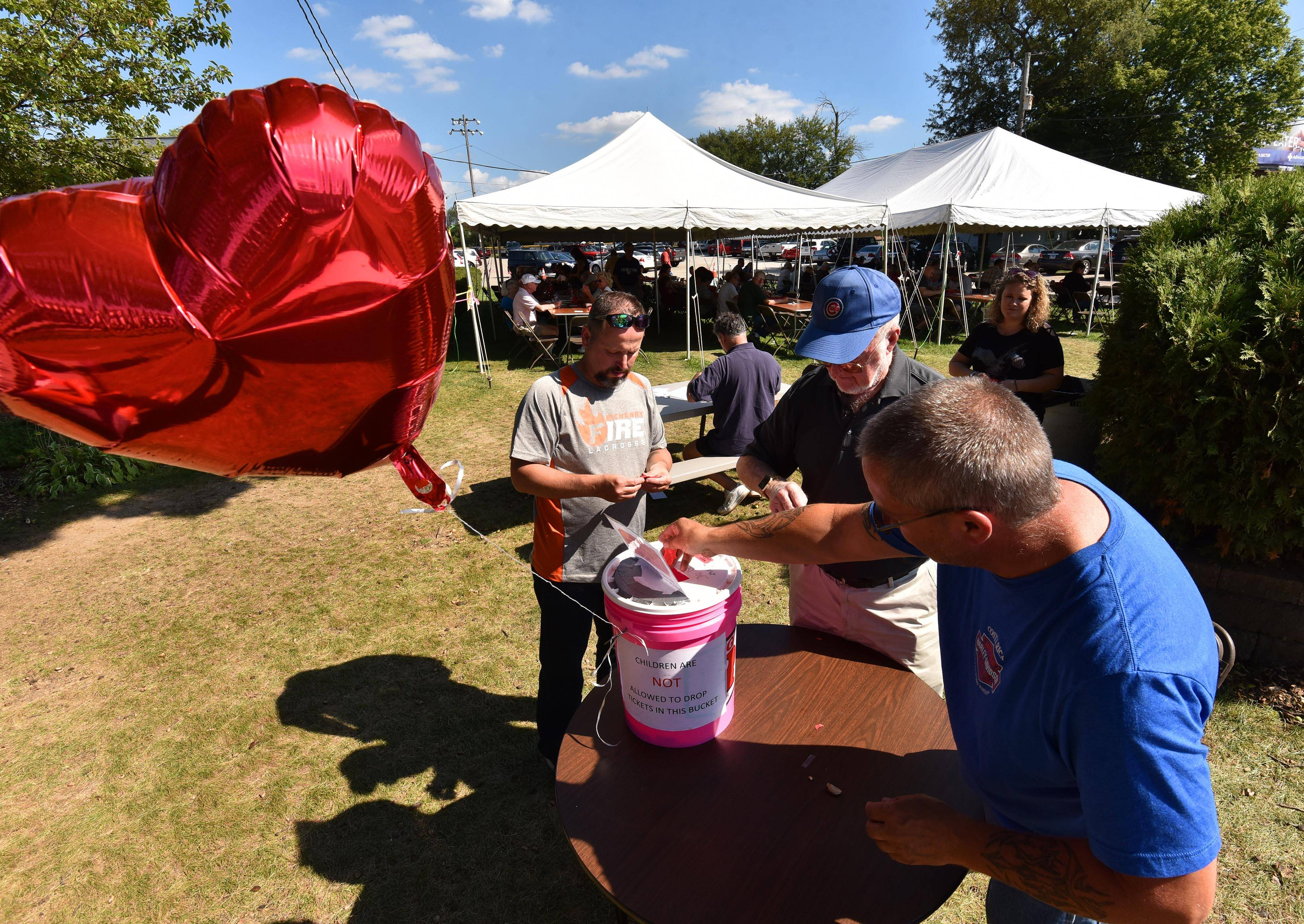 People drop their completed tickets into buckets as others add their information under tents Wednesday for next week's final Queen of Hearts raffle at the McHenry VFW Post 4600.