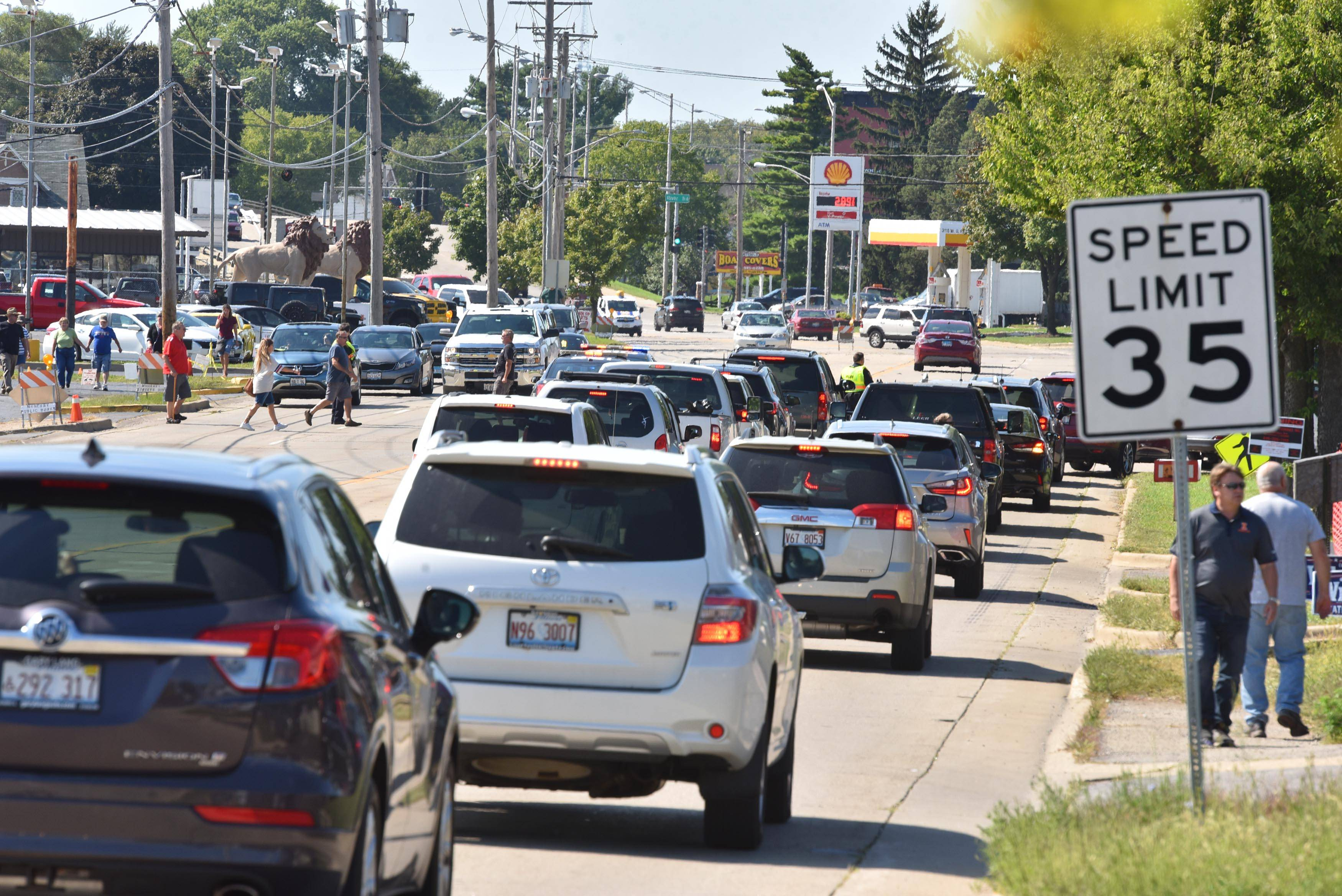 Police stop traffic on Route 120 to let people from remote parking lots stand in line Wednesday for tickets for next week's final Queen of Hearts raffle at the McHenry VFW Post 4600.
