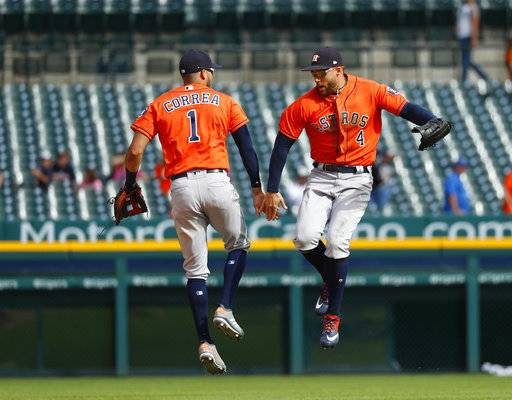 Houston Astros' Carlos Correa (1) and George Springer (4) celebrate their 5-4 win after a baseball game against the Detroit Tigers in Detroit, Wednesday, Sept. 12, 2018.
