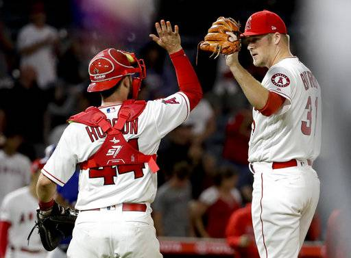 Los Angeles Angels catcher Joe Hudson and pitcher Ty Buttrey celebrate after their 1-0 win over the Texas Rangers after a baseball game in Anaheim, Calif., Tuesday, Sept. 11, 2018.