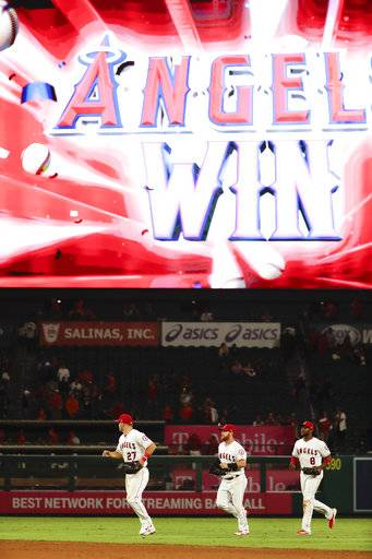 Los Angeles Angels center fielder Mike Trout, from left, right fielder Kole Calhoun and left fielder Justin Upton run off the field after their win against the Texas Rangers during a baseball game in Anaheim, Calif., Tuesday, Sept. 11, 2018.