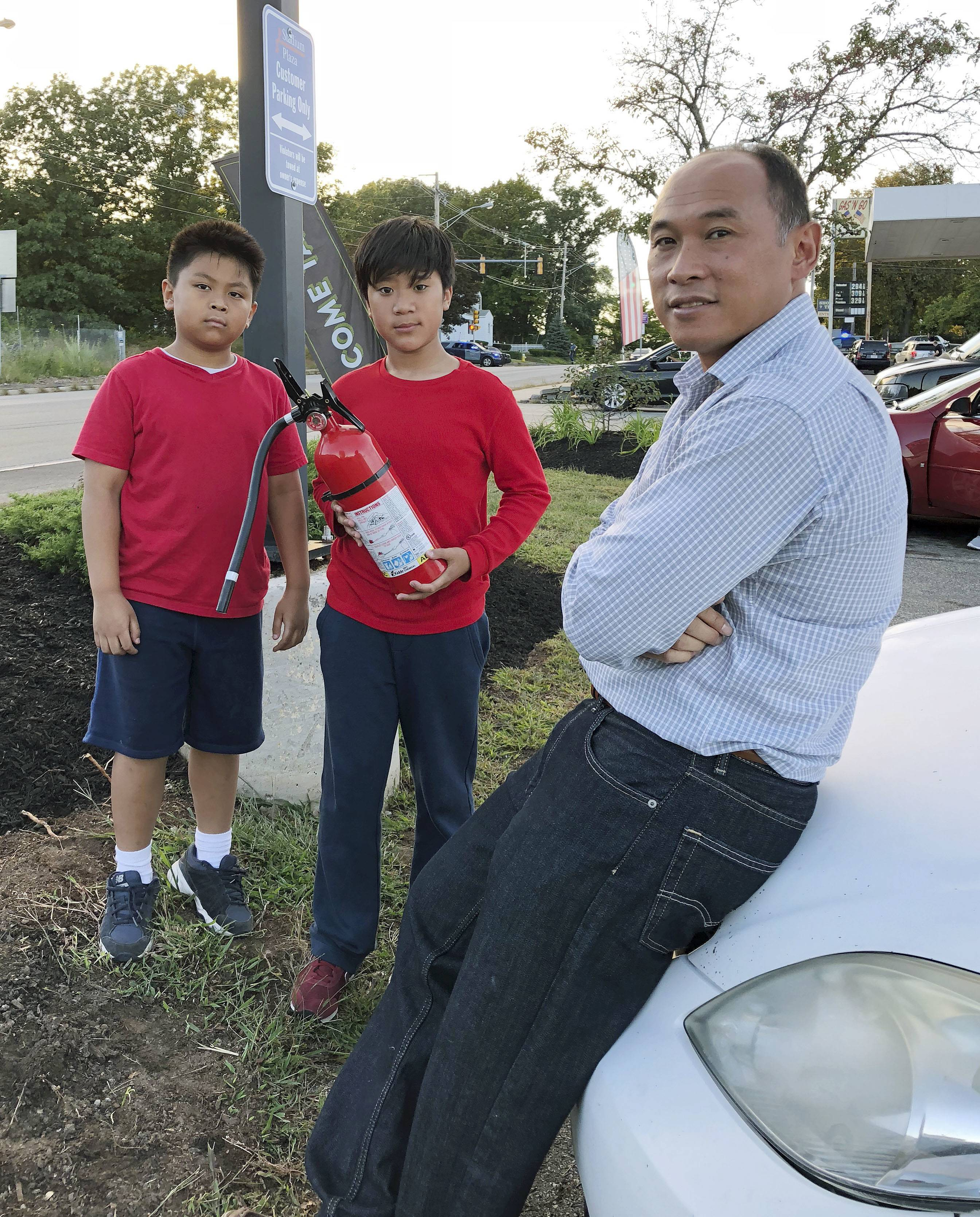 Ra Nam, right, with his sons Evan, left, and Tristan, center, wait in a parking lot outside their Colonial Heights neighborhood which was evacuated Thursday, Sept. 13, 2018, in Lawrence, Mass., due to fires and explosions triggered by a problem with a gas line that feeds homes in several communities north of Boston.