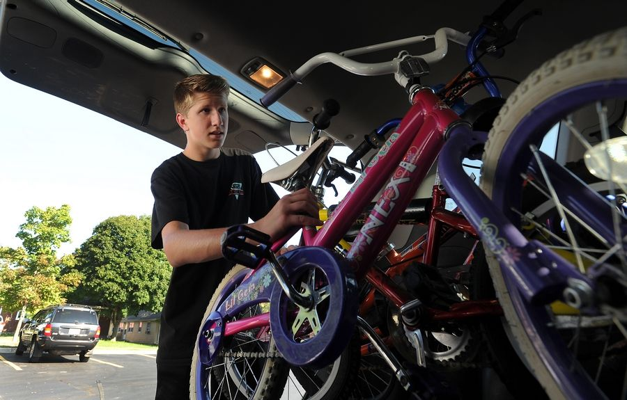 Jacobs High School senior Justin Lorenz unpacks a van loaded with several bikes in Carpentersville which were just a few of the over 60 he collected from various sources for the Boys and Girls Clubs of Dundee Township.