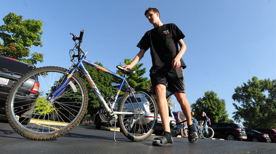 Jacobs High School senior Justin Lorenz wheels out a donated bike, one of over 60 he collected for the Boys and Girls Clubs of Dundee Township, in Carpentersville on Thursday.