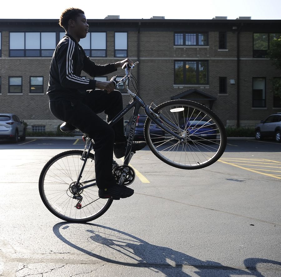 Eighth-grader Terrence Lampley, 15, tries out the new bike he picked up as part of Jacobs High School senior Justin Lorenz's donation drive.