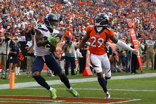 FILE - In this Sunday, Sept. 9, 2018, file photo, Seattle Seahawks wide receiver Brandon Marshall, left, hauls in a touchdown pass in the end zone as Denver Broncos defensive back Bradley Roby (29) looks on during the second half of an NFL football game in Denver. Marshall's debut with his sixth team went well in Week 1, even though Seattle ended up losing 27-24 to the Broncos. The 34-year-old had three receptions for 46 yards and a touchdown in his Seattle debut.