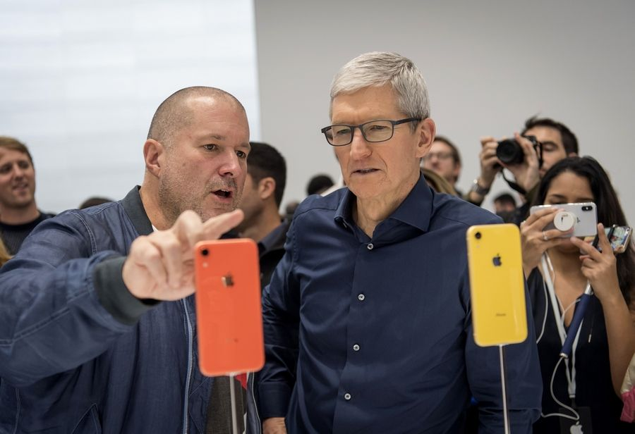 Jony Ive, chief design officer for Apple, left, and Tim Cook, chief executive officer, view a new iPhone during Apple's annual product event.