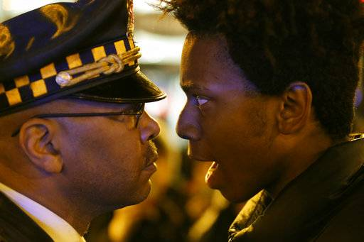 "FILE - In this Wednesday, Nov. 25, 2015 file photo, Lamon Reccord, right, stares and yells, ""Shoot me 16 times,"" at a Chicago police officer as he and others march through Chicago's Loop, one day after murder charges were brought against police officer Jason Van Dyke in the killing of 17-year-old Laquan McDonald."