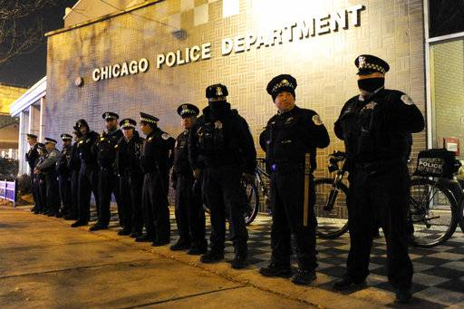 FILE - In this Tuesday, Nov. 24, 2015 file photo, police officers line up outside the District 1 central headquarters at 17th and State streets in Chicago, during a protest for 17-year-old Laquan McDonald, who was fatally shot in October 2014. Chicago Police Officer Jason Van Dyke was charged with first-degree murder in the killing.