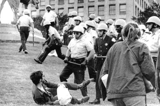 FILE - In this Aug. 26, 1968 file photo, Chicago police officers wielding nightsticks confront a demonstrator on the ground in Grant Park after protesters against the Vietnam War climbed on the statue of Civil War Gen. John Logan. It was one of many protests during the tumultuous 1968 Democratic National Convention.