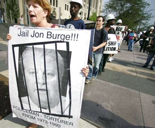 FILE - In this June, 16, 2006 file photo, Kristin Roberts, left, holds a sign of former Police Commander Jon Burge as she and others stage a protest outside the Cook County courthouse in Chicago, demanding the release of a report on allegations that some Chicago police officers tortured suspects. Burge led a crew of detectives accused of torturing more than 100 suspects, mostly black men, from 1972 to 1991, shocking them with cattle prods, smothering them with typewriter covers and shoving guns in their mouths to secure confessions.