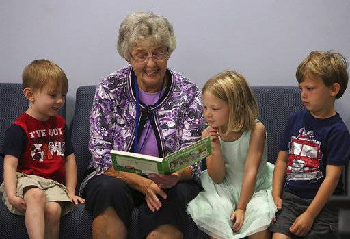 "In this Aug. 28, 2018 photo, volunteer Sylvia Baxter reads the book ""Percy's Promise"" to  children Michael, left, and twins Ava and Matthew, as part of the Ready Set Grow program, at the Adams County Health Department in Quincy, Ill. The program is coordinated by the Regional Office of Education, and emphasizes the importance of parents reading to their children. (Phil Carlson/The Quincy Herald-Whig via AP)"