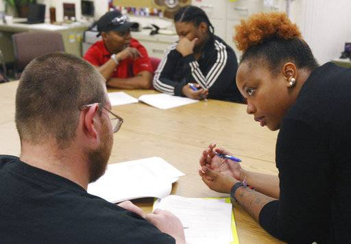 In this Aug. 23, 2018 photo, administration counselor Karlesia Pickett assists Jonathan Sweet  as he fills out paperwork along with Rakia Joyner, Khalilah Land, during the monthly Job Corps orientation at Old King's Orchard Community Center in Decatur, Ill. Job Corps, a program administered by the U.S. Department of Labor that offers free-of-charge education and vocational training to men and women ages 16 to 24. Old King's Orchard has been hosting the monthly meetings for more than a year.(Jim Bowling/Herald & Review via AP)
