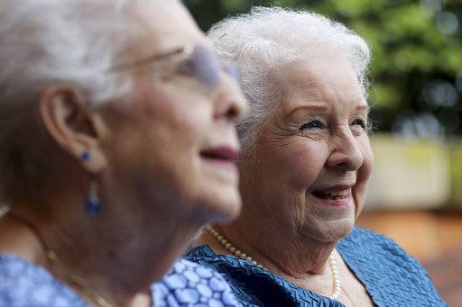 "In this Aug. 21, 2018 photo, Jean Harrison, left, of Algonquin and Jane Umbarger of McHenry,  right, known as the ""incubator twins"", talk about their experiences in McHenry, Ill. The twin sisters, both 84, were among hundreds of premature infants who were placed in incubators at the Century of Progress expo in Chicago in 1933 and 1934. They also had a double wedding in 1953, which drew national attention. The sisters are featured in a new book by Dawn Raffel, titled ""The Strange Case of Dr. Couney: How a Mysterious European Showman Saved Thousands of American Babies."" (Matthew Apgar/Northwest Herald via AP)"